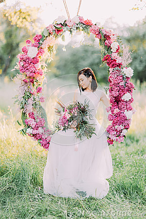 Free The Bride With The Hair Accessories Holding The Bouquet Of Peonies, Looking At The Ground And Sitting In The Wedding Royalty Free Stock Photo - 97732435