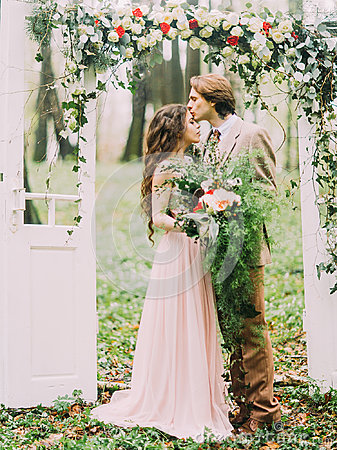 Free The Close-up Vertical Photo Of The Groom In Vintage Suit Kissing His Bride With The Big Bouquet Into The Forehead Under Stock Image - 98016761