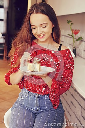 Free The Girl In The Bakery Eats Dessert. Beautiful Model In A Cafe Eats Sweets And Smiling. Beautiful Girl In A Red Sweater Stock Photo - 133555350