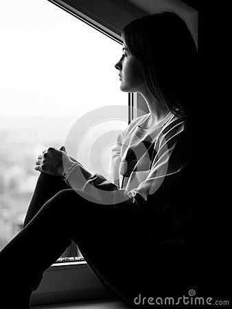 Free The Girl Is Near The Window. A Look In The Distance And Mysterious Thoughts. Stock Photos - 99347123