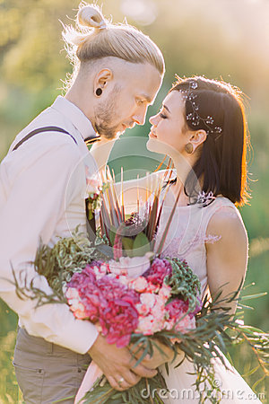 Free The Lovely Close-up Portrait Of The Newlyweds Close To Each Other And Holding The Pink Bouquet In The Sunny Forest. Stock Photos - 98844603