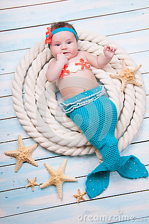 Free The Newborn Girl In A Mermaid Costume, Lies In The Ropes On Wooden Boards. Stock Photo - 84850590