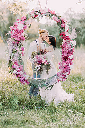 Free The Newlywed Couple Is Kissing Behind The Wedding Peonies Arch In The Sunny Wood. Close-up Portrait. Royalty Free Stock Photos - 97732278