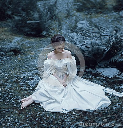 Free The Princess Sits On The Ground In The Forest, Among The Fern And Moss. An Unusual Face. On The Lady Is A White Vintage Royalty Free Stock Images - 112139789