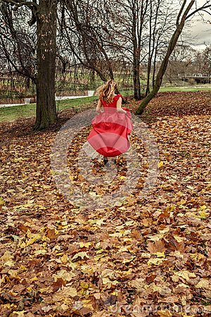 Free The Runaway Bride The Girl In A Red Dress Runs Along The Fallen Autumn Leaves Before The Storm Stock Images - 103868744