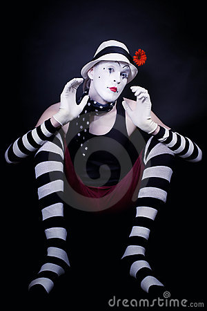 Theatrical mime with red flower sits