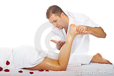 Therapist man massaging woman s leg