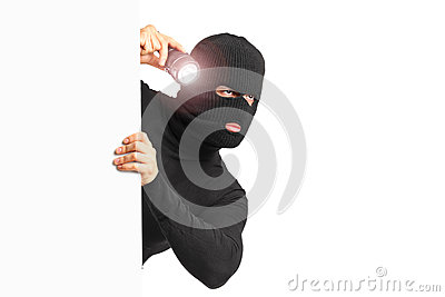Thief with holding a flashlight behind a white pa