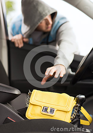 Thief stealing bag from the car