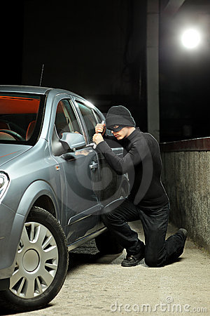 Thief wearing a robbery mask trying to steal a car