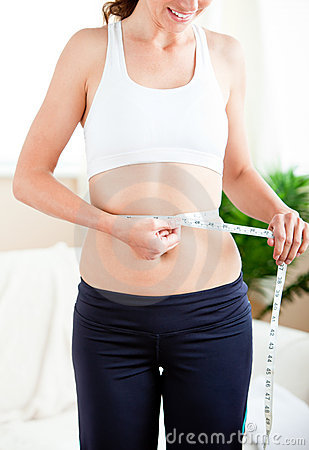 Thin hispanic woman measuring her waist with tape