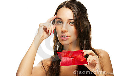 Thinking beautiful woman holding red present
