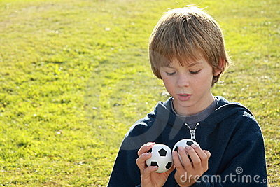 Thinking boy with two balls