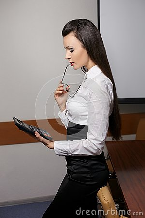 Thinking business woman with calculator in office