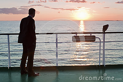 Thinking businessman and red sunset on a ferry