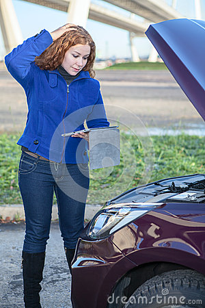 Thinking woman with opened car cowling