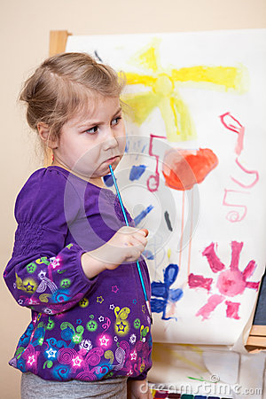Thinking young girl standing with painting brush