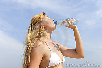 Thirsty woman drinking water outdoors