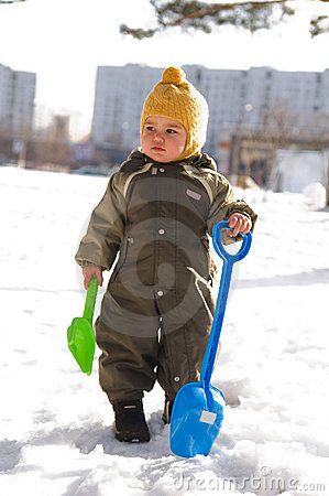 Thoughtful baby with shovels against buildings