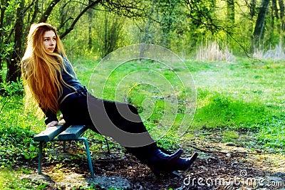 Thoughtful beautiful woman relaxing on park bench