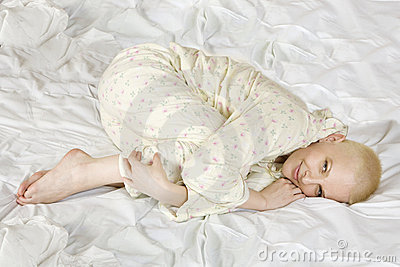 Thoughtful blond bald woman lying on the bed