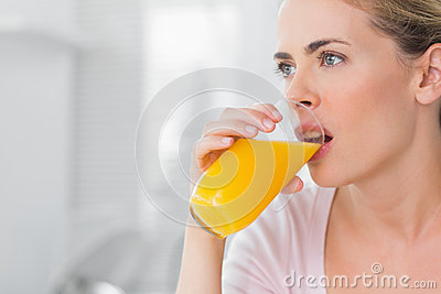 Thoughtful blond woman drinking orange juice