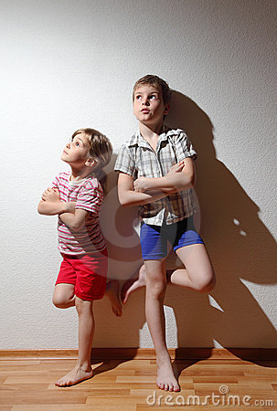 Thoughtful boy and girl stand with folded hands