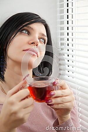 Thoughtful brunette girl drinking tea