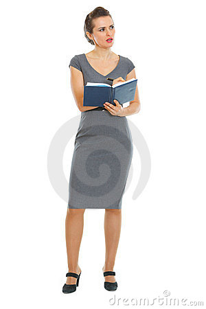 Thoughtful business woman writing in notebook