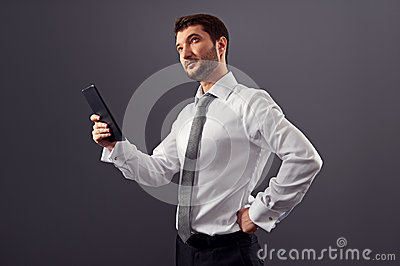 Businessman holding tablet pc and looking up