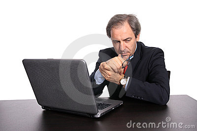 Thoughtful businessman with laptop at his desk
