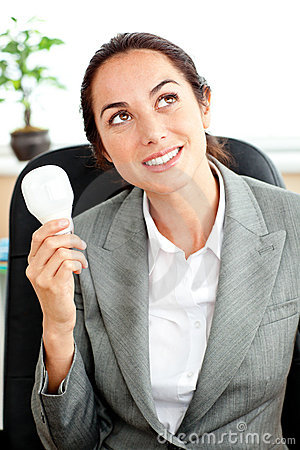 Thoughtful businesswoman holding a light bulb
