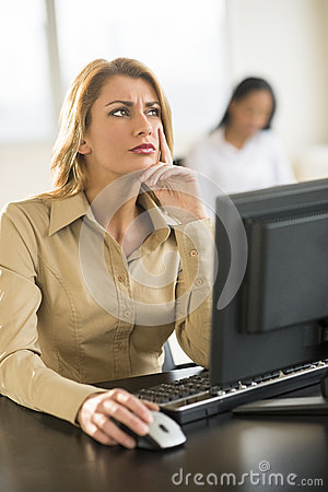 Thoughtful Businesswoman Using Computer At Desk