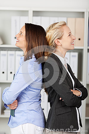 Thoughtful Businesswomen Standing Back To Back