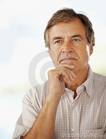 Thoughtful elderly man with hand on chin