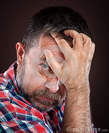 Thoughtful elderly man with hand near the face