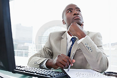 Thoughtful entrepreneur while working with a computer