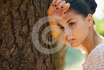 Thoughtful girl lean against tree