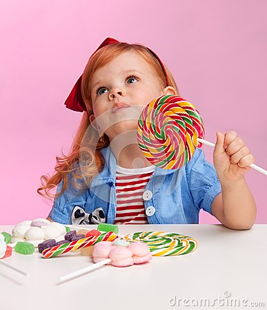 Thoughtful girl with lollipop
