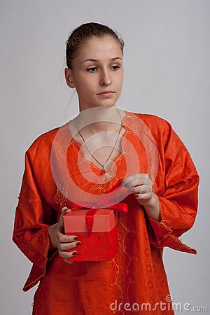 Thoughtful girl in an orange dress opens a gift