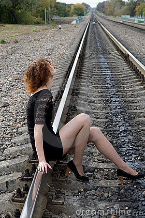 Thoughtful girl sitting on rails