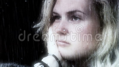 Thoughtful girl. Young girl looking out of a window a rainy day, looking sad stock footage
