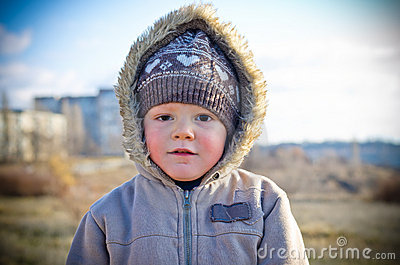 Thoughtful little boy on walk in the autumn