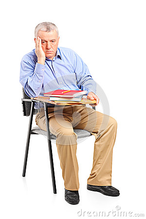 Thoughtful mature man sitting on a classroom chair