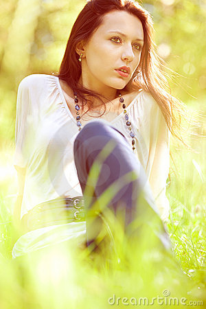 Free Thoughtful Pretty Girl Sitting On Green Grass Stock Photography - 20912732