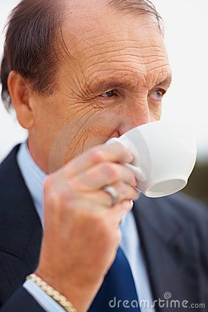 Thoughtful senior business man drinking tea