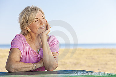Thoughtful Senior Woman Sitting Outside at Table