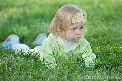 Thoughtful toddler is crawling in the green grass