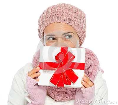 Thoughtful woman  hiding behind Christmas gift