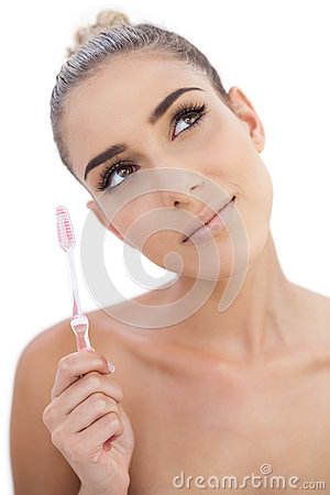 Thoughtful woman holding a toothbrush